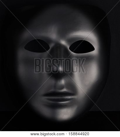 Anonymous Black Mask Protruding From Pitch Black Background.