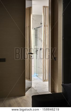 Entrance to the bathroom in the interior in a modern style. There is a wooden wall with a specular door, parquet on the floor. Bathroom tiled with white tiles and has a shower with glass door.