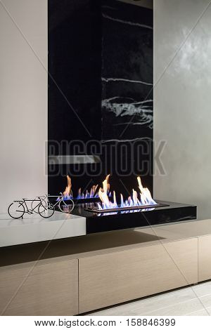 One black and one white small decorative bicycles on the white rack next to the black burning fireplace in the modern interior. Under the fireplace there are wooden lockers. Parquet is on the floor.