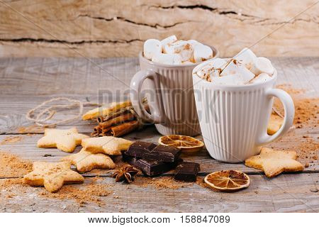 cup of hot cocoa with marshmallows, cinnamon and chocolate on wooden background