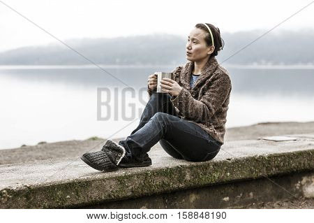 Woman sits on ledge and relaxes by lake.
