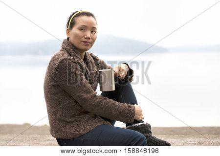 Asian woman enjoys coffee by a lake.