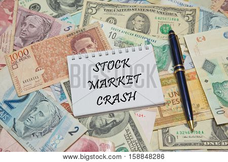 Notebook page with text STOCK MARKET CRASH, background from different world Currencies