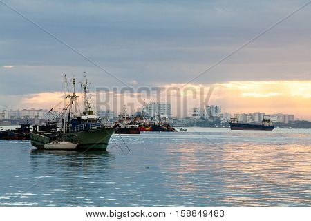 Sunrise by the shore with view of commercial and fishing boat