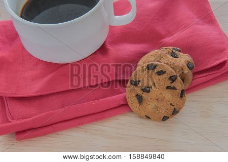 Chocolate chip cookie on a cloth and coffee on wood background.