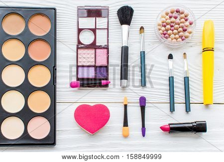 set of colorful decorative cosmetics on wooden background top view.