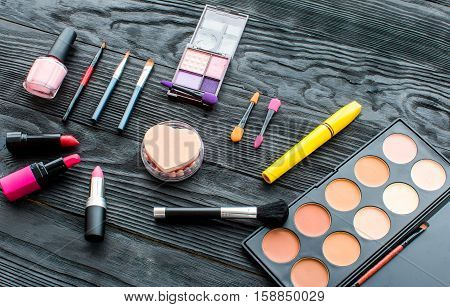 set of colorful decorative cosmetics on dark wooden background top view.
