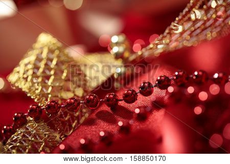 red glass beads close-up on golden with satin ribbon and blurred lights bokeh  background