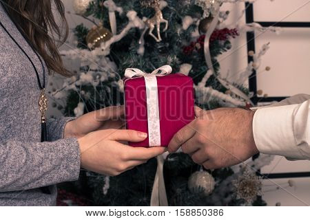 Hands of man giving a Christmas gift to girlfriend