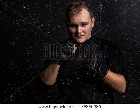 Portrait of boxer fighting in the rain in aquastudio with drops