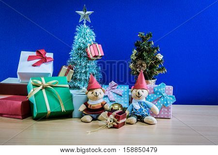 Ornament and a couple lovely teddy bear Christmas decorate at Merry Christmas and happy new year night light. Christmas tree and other decoration with Lovely gift and ribbon .