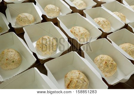 Ground-meat cutlets in cardboard boxes on table.