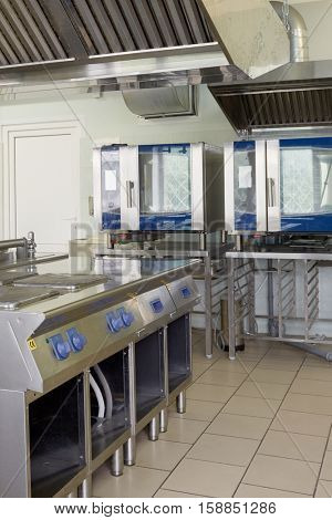 Kitchen room with stoves, heat ovens and refrigerators in restaurant.