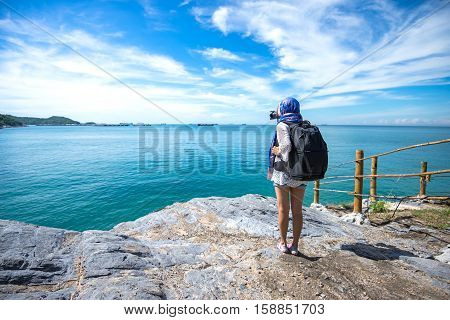 Female photographer taking pictures of the beautiful beach and blue sky