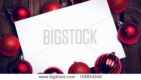 Red christmas baubles surrounding white page against overhead of wooden planks