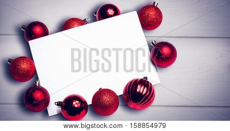 Red christmas baubles surrounding white page against white wooden background