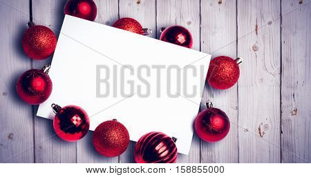 Red christmas baubles surrounding white page against wooden background