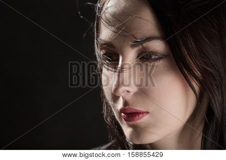 sad woman with blowing hair portrait on black background with copyspace