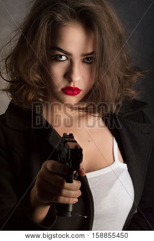 serious girl with gun aiming with gun on black background