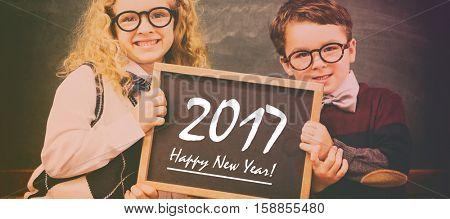 School kids holding chalkboard with new year text against blackboard