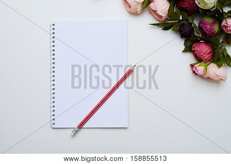A mid shot of ring-bound notebook and red long pencil on it. Splendid peonies placing on right side above