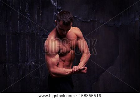 Shirtless athletic man is flexing muscles showing great relief of his arms and torso isolated against dark wall