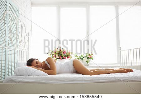 Sexy slim woman in white underwear is sleeping on bed with white sheets in white room with flowers on the windowsill