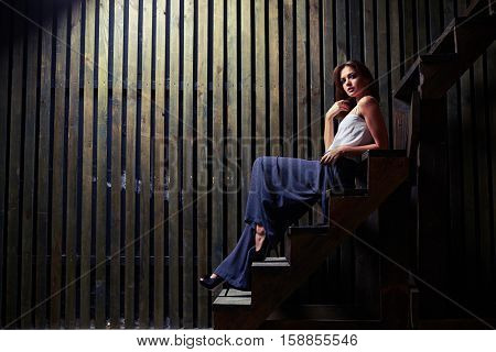 Wide shot of sensual brunette sitting on staircase, holding a hand near face while posing in studio. Wearing white satin top and a long pair of culottes in pattern