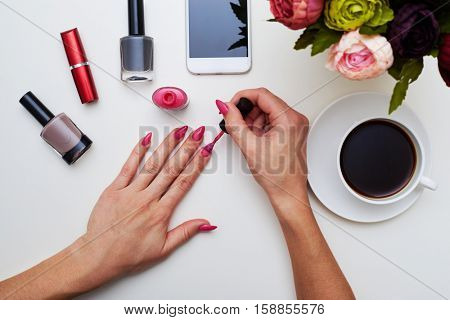 A mid shot of manicured in pink fingers of a lady. Nail polishes, lipstick, cup of coffee, bunch of peonies over flat layout