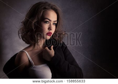 sensual sad young woman undressing on black background