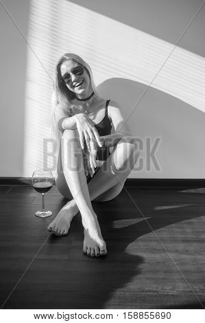 happy blond girl with wineglass sitting in sunlight on floor, monochrome