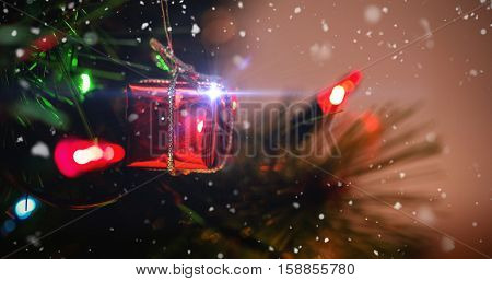 Snow falling against fairy light and small gift box hanging on christmas tree