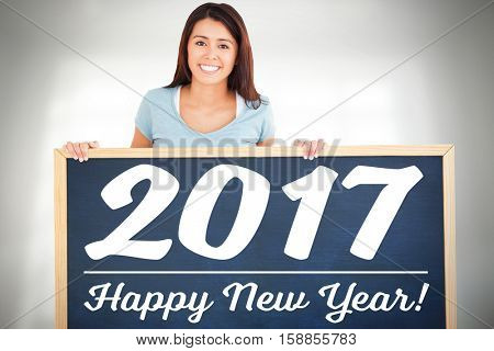 woman holding a black board with new year text against a white wall