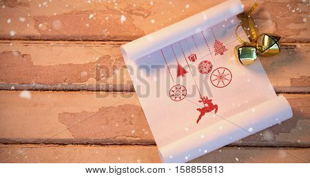 Snow falling against bells and paper on wooden plank
