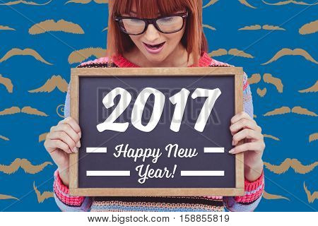 Smiling hipster woman holding blackboard with new year text
