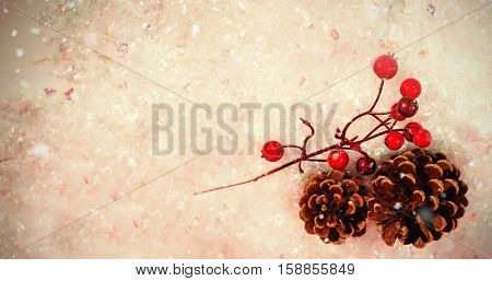 Snow falling against pine cone and red cherry on snow