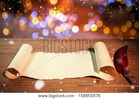 Snow falling against high angle view of old blank scroll paper and quill