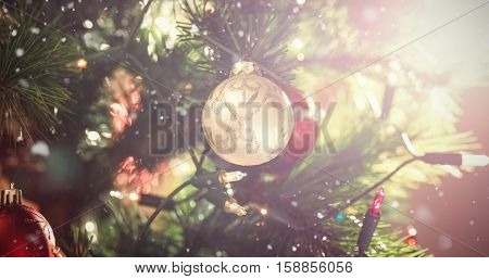 Snow falling against decorations on christmas tree