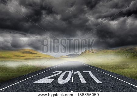 Happy New Year 2017 against 3D stormy landscape background with street