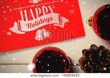 Snow falling against red christmas bauble and pine cone on wooden table