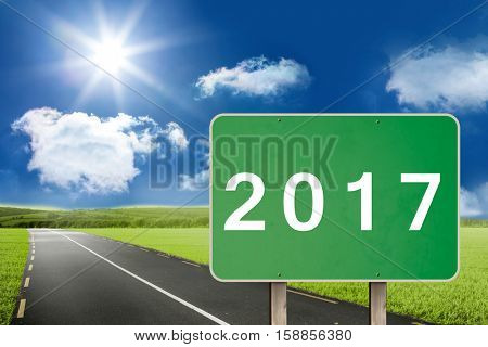Digital image of new year 2017 against road leading out to the horizon