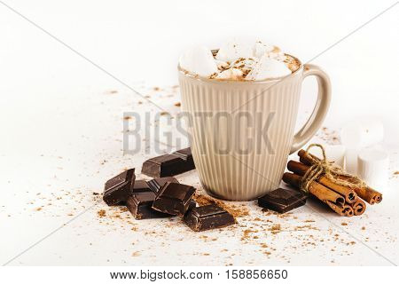 cup of hot cocoa with marshmallows, chocolate and cinnamon on a white background