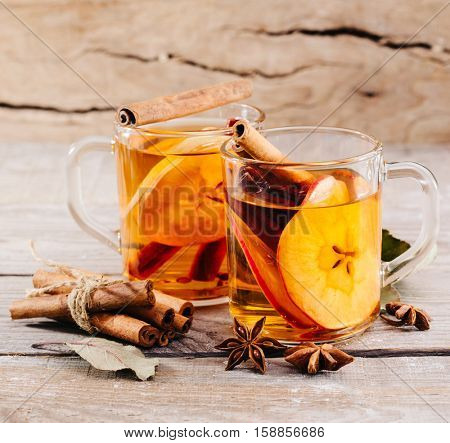 hot apple cider with cinnamon, anise and orange on a wooden background