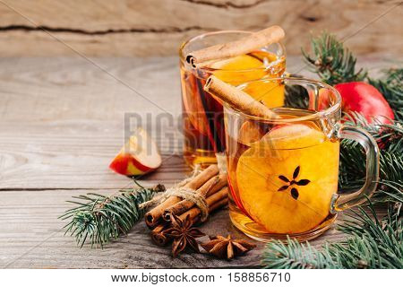 Christmas hot apple cider with cinnamon, anise and orange on a wooden background