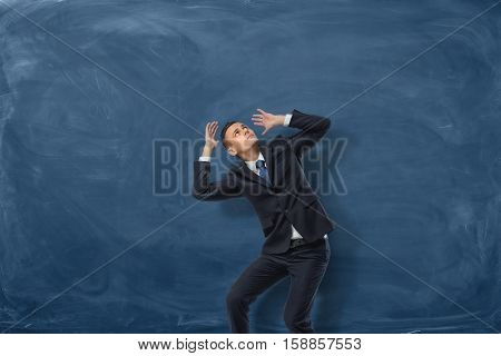 Businessman standing in desparate pose on blue chalkboard background. Problems and issues. Protection and defense. Psychological burden and stress.