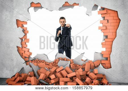 A businessman standing near the hole in the wall which he has just made with a hard punch, a pile of red bricks are lying beneath. Overcoming obstacles. Business issues. Economic development.