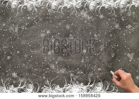 Blackboard with a hand starting to write. Christmas concept