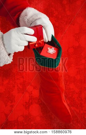 Santa Claus putting presents in Christmas stockings against red paint splatter background
