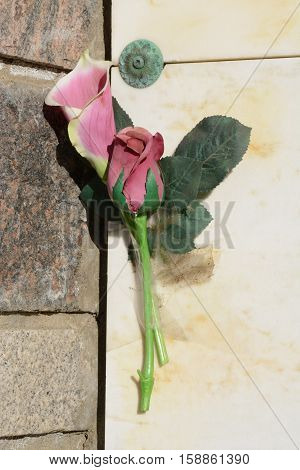 All weather artificial red rose and pink calla lily flowers taped onto mausoleum wall as memorial to loved one