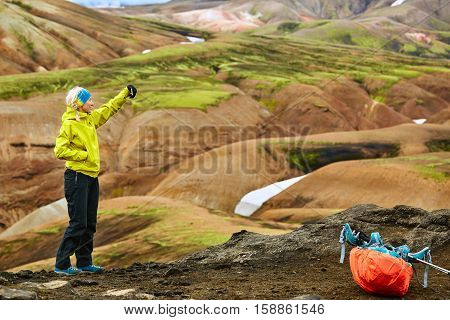woman hiker photographer taking selfie on the rhyolite mountains background in Iceland